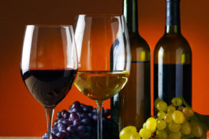 A picture of two glasses of wine, two bottles of wine, with green and purple grapes.