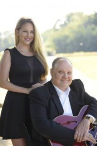 A woman standing next to a man holding a guitar