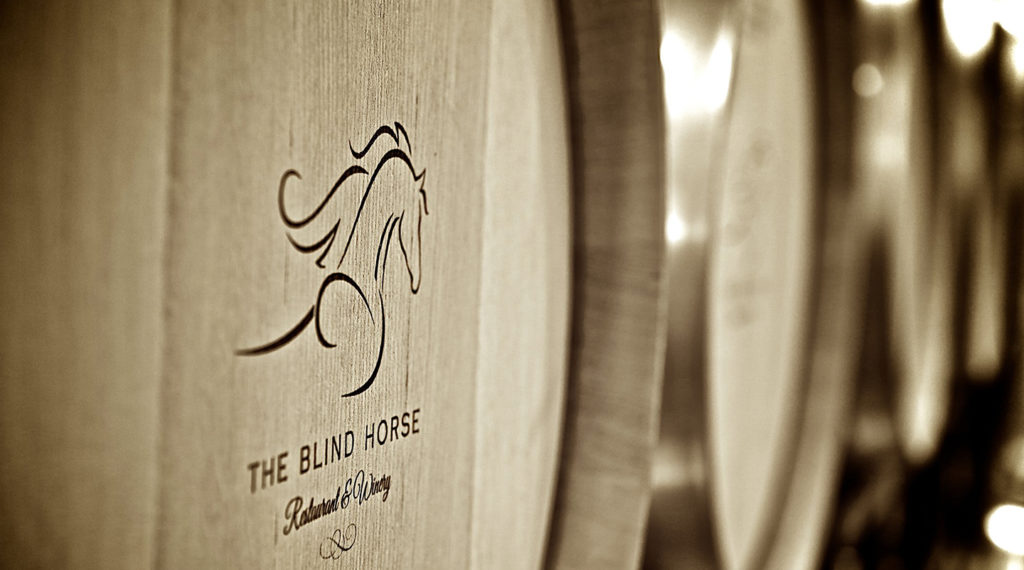 A picture of The Blind Horse logo on wine barrels