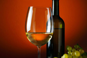A picture of a wine glass, wine bottle and green grapes.